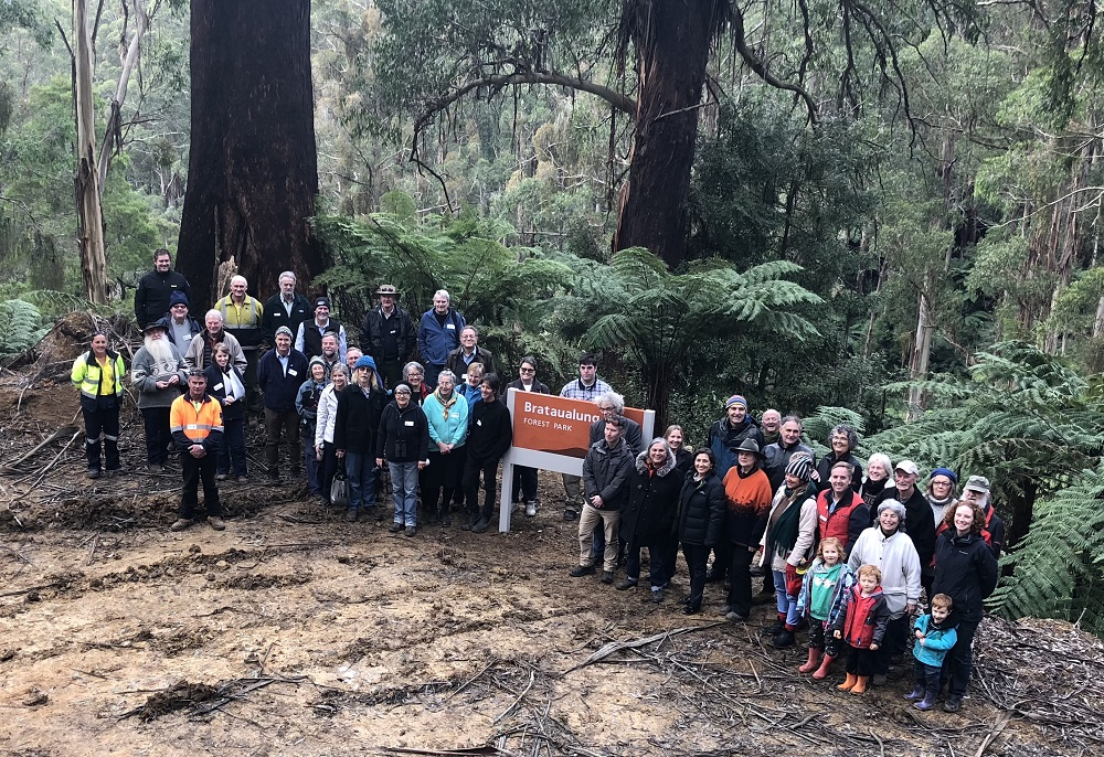 Picture of community groups in front of the Brataualung Forest Park sign